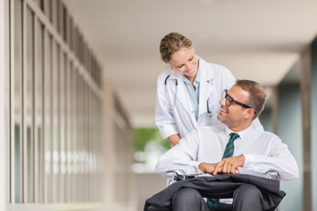 Photo of female doctor pushing businessman on wheelchair