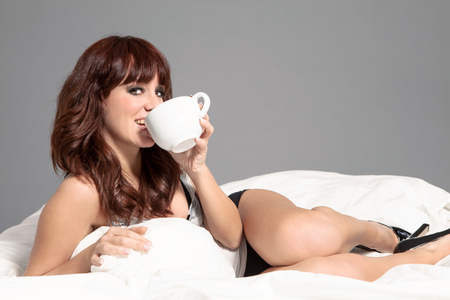 brunette woman is drkining coffee in the bed while smiling towards the camera photo