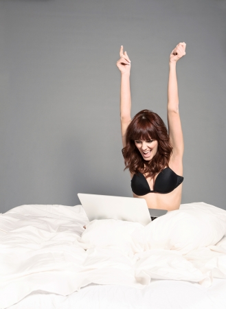 raised arms: Happy screaming woman with notebook in her bed wearing lingerie Stock Photo