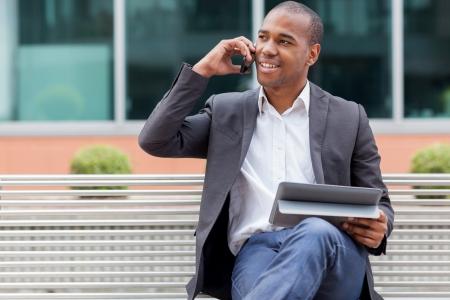 Sourire afro gestionnaire américain assis sur un banc et téléphoner