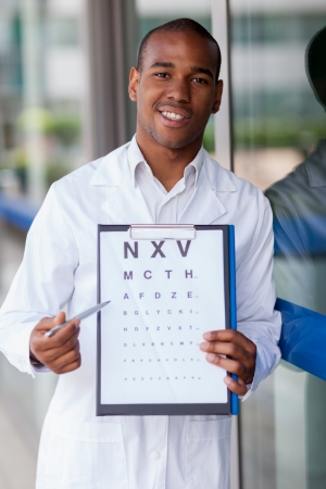 astigmatism: Smiling afro american oculist with flip chart