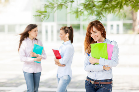 Three female students with notebooks are smiling photo