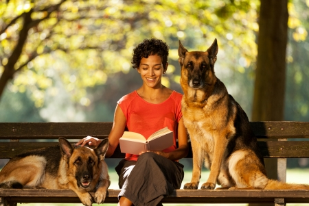 Image of woman sitting on a bench with two german shepherds