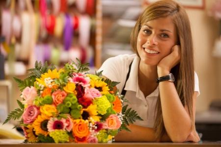 vendeurs: Belle fleuriste souriant dans son magasin avec bouquet color�