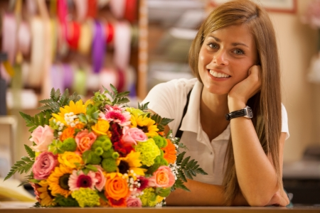 Beautiful smiling florist in her store with colorful bouquet