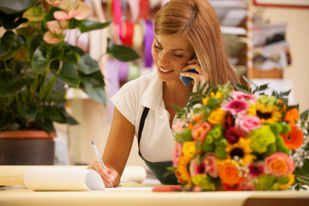 Florist at the phone with customers for aranging orders photo
