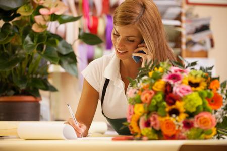 Florista en el teléfono con los clientes para aranging pedidos