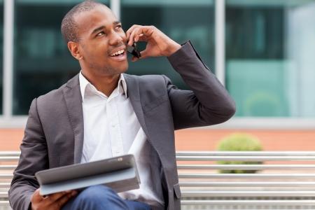 笑顔のアフロ アメリカン マネージャーのベンチに座っていると、電話をかけ