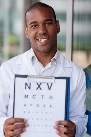 oculista: Sonriendo afro americano oculista con rotafolio Foto de archivo