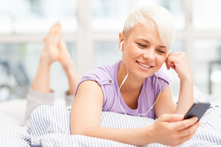earphone: Photo of young woman phoning in the bed with headphones Stock Photo