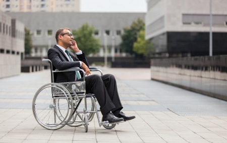 電話をかけ、車椅子に実業家の写真