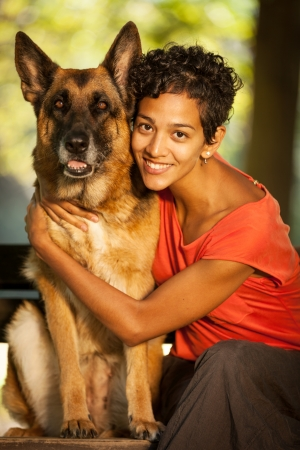 Smiling woman is hugging her german shepherd while seated on a bench photo