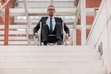 Conceptual photo of businessman on wheelchair in front of stairs