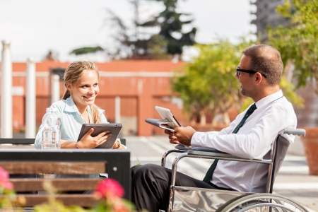Photo of businessman on wheelchair talks to his colleague