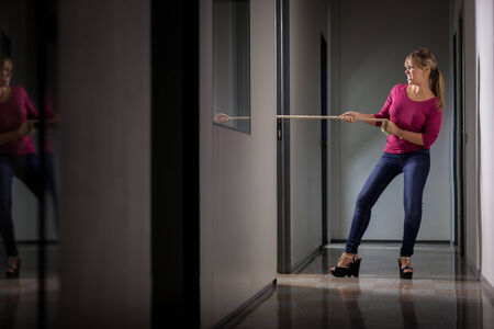 woman rope: Conceptual photo of angry woman pulling a rope symbolizing business competition