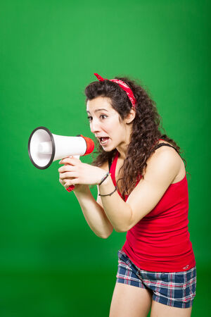 Photo of young woman screaming through megaphone over green background Stock Photo - 24146646