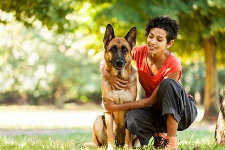 mujer con perro: Foto de la mujer con un pastor alemán en un campo de hierba