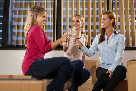 Three beautiful woman are sitting on boxes while celebrating their new business start photo