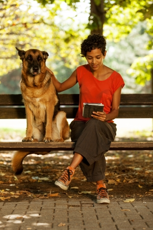 Photo of woman looking a digital tablet while german shepherd is seated next to her photo