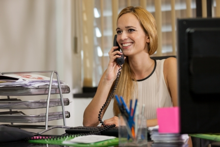 Smiling businesswoman working in the office while phoning Stock Photo