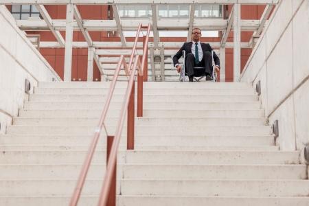階段の前に車椅子で実業家の概念的な写真 写真素材
