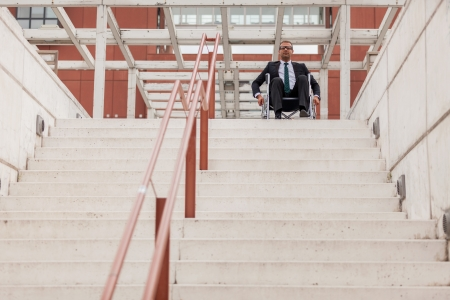 Conceptual photo of businessman on wheelchair in front of stairs photo