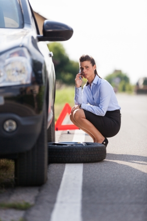 car trouble: photo of businesswoman with flat tire