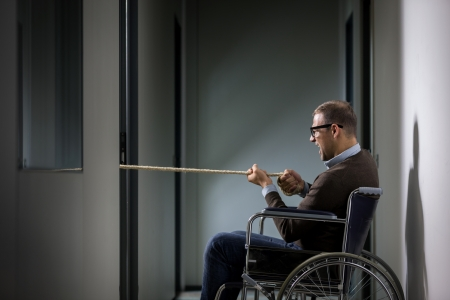 carreer: Conceptual photo of man on wheelchair is pulling a rope symbolizing business competition