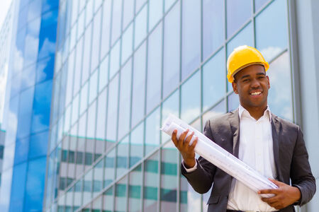 Afro american construction engineer in front of building holding blueprints photo