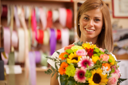 Beautiful smiling florist in her store with colorful bouquet  photo