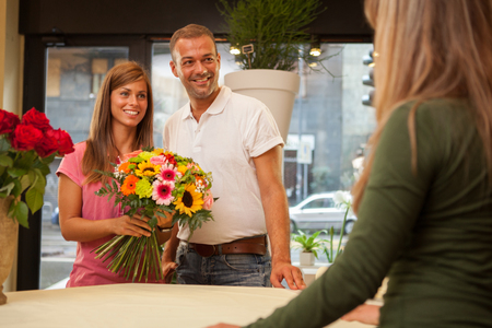 Couple at the flower shop with a bunch of flowers in their hands photo