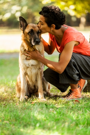 sitter: Photo of woman with a german shepherd in a grass field