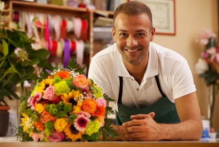 カラフルな花束の横に立っている笑顔の花屋の写真