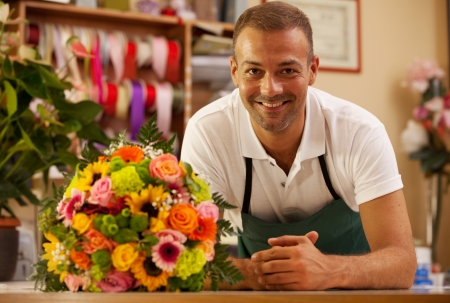 Photo of smiling florist standing next to a colorful bouquet Stockfoto