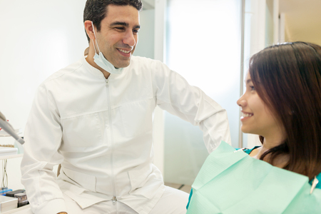 oral communication: photo of asian male dentist speaking with his female patient in the office Stock Photo