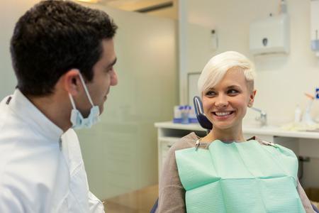 comunicacion oral: foto de dentista hombre europeo que habla con su paciente de sexo femenino rubio