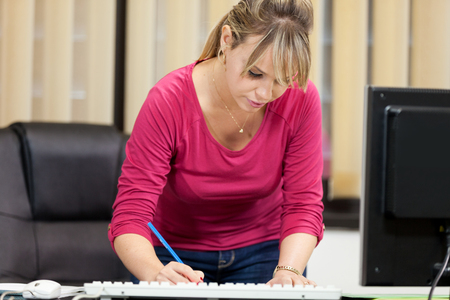 ner: photo of young secretary taking notes while standing next to ner desk in office