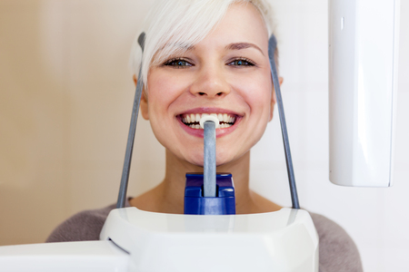 medical technical equipment: photo of caucasian smiling woman doing a dental scan