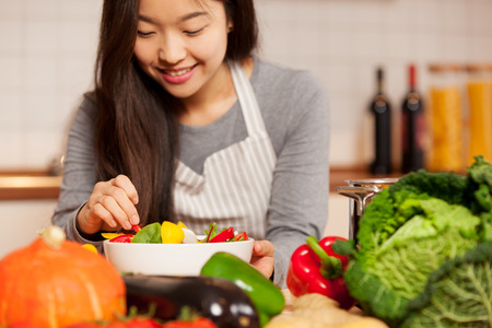 asian young woman composing a colorful salad at home in the kitchen
