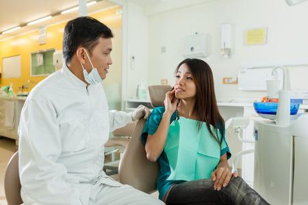 彼女は歯科医彼女が痛みを持っていることを説明するアジアの女性患者 写真素材
