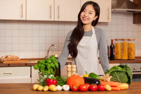asian young woman standing in the kitchen with colorful ingredients on the table