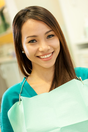 photo of smiling asian woman at the dentist looking towards the camera