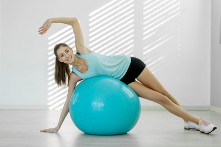 fit ball: young smiling woman doing workout with a gym ball Stock Photo