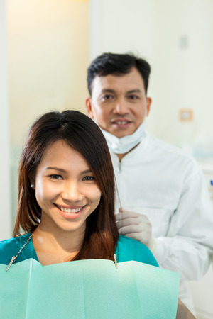 health check: male dentist with his asian patient that looking towards the camera and smiling