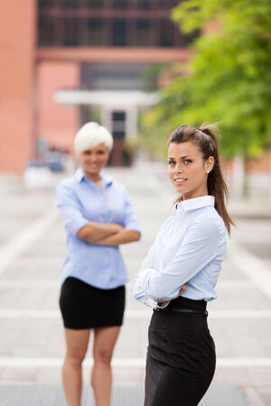 next to each other: two businesswoman standing next to each other outdoors