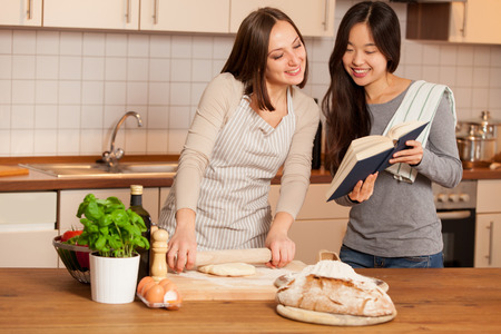 smiling caucasian woman working on a dough while her friend is reading a cookbook