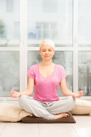 meditation room: photo of caucasian blonde woman doing meditation on the floor at home