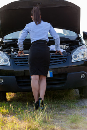 car trouble: Photo of caucasian businesswoman looking inside the car hood