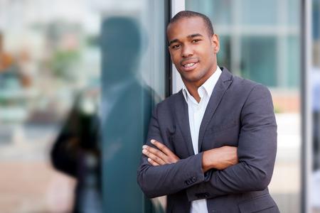 ガラスの壁の横に立っている笑顔のアフリカの実業家の写真 写真素材