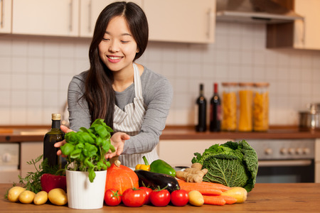 photo of asian young woman standing in the kitchen with colorful ingredients on the table